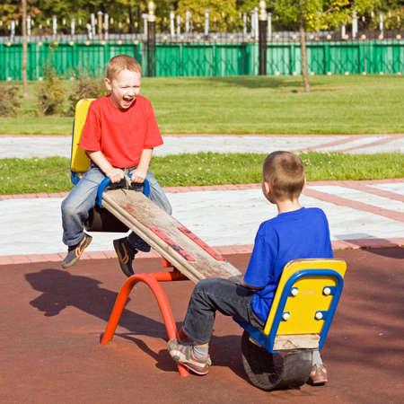 Afspelen op een wip op een speel tuin in een zonnige dag jongens Stockfoto