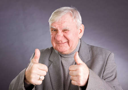 75s: senior man showing thumb up on a isolated white background