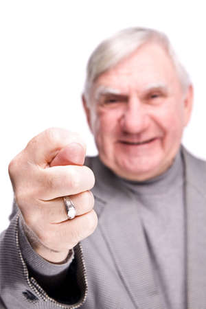 75s: senior man showing fig on a isolated white background