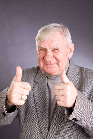 75s: senior man showing thumb up on a grey background