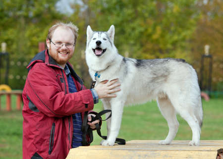 blue eye husky: Man with a dog breed Siberian Husky