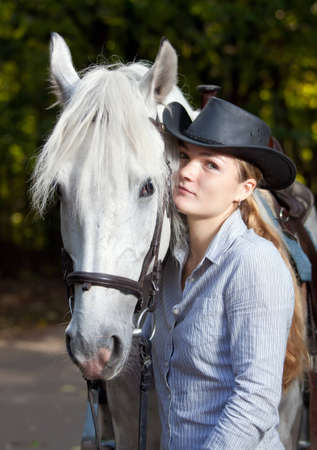Young Lady in hat hugging her horse photo