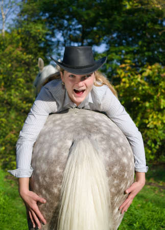 Young Lady in hat riding a horse photo