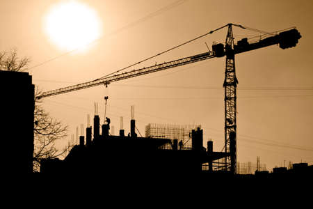 Silhouette of construction site against the orange sky Stock Photo