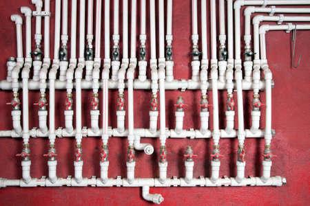 tuberias de agua: Tuber�as de aguas blancas contra un muro rojo Foto de archivo