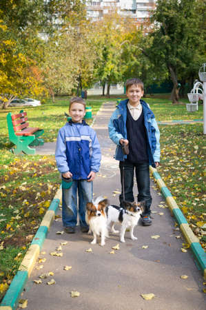 Two boys with dogs in autumn park photo