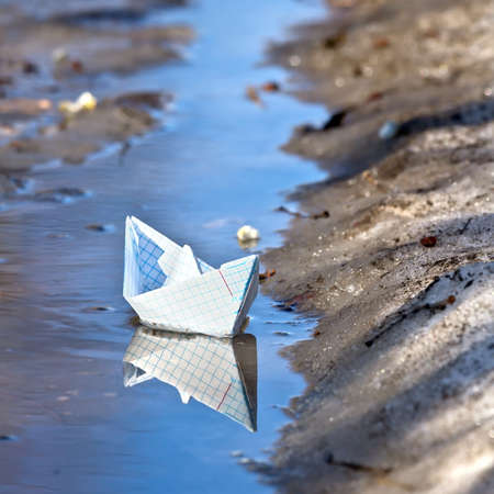 Toy boat of paper in the water  photo