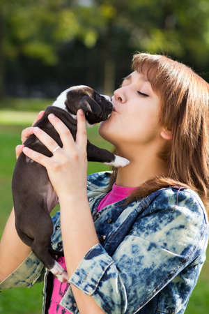 amstaff: Girl kissing her puppy American Staffordshire Terrier