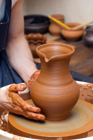 craft product: Close-up of hands making pottery on a wheel Stock Photo