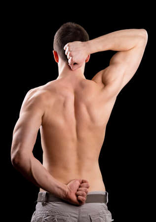 triceps: Man shows biceps on a black background