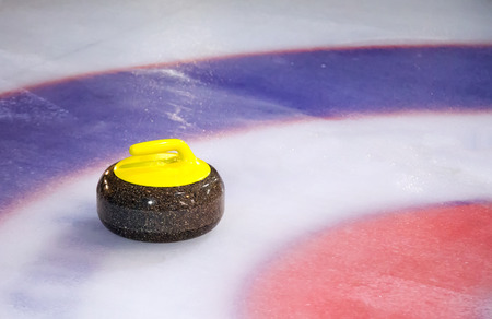 A single curling stone on the ice of a curling rink