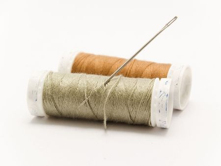 threaded needle and cotton reel
