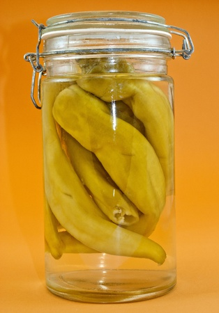 Chili peppers marinated in the glass jar isolated on the white background photo