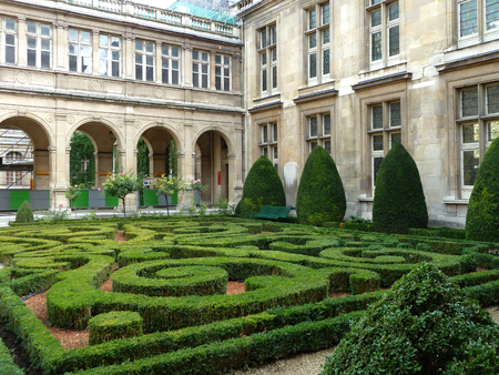 A manicured formal garden maze of boxwoods and holly trees is contained in a Paris courtyard Editorial