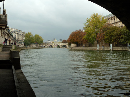 View of Siene River in Paris from beneath a bridge along the Quai on a cloudy day Stock Photo