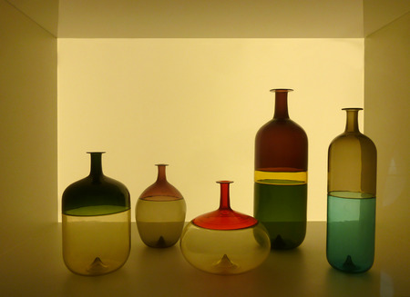 Composition of colored and shaped bottles inside a golden translucent box