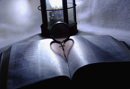 lamp light: Heart silhouette on bible by old fashion lamp light Stock Photo
