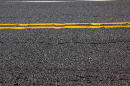 the road surface: asphalt road surface with yellow stripes Stock Photo