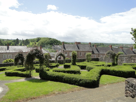 Gardens with shaped shrubs and estate houses in the background