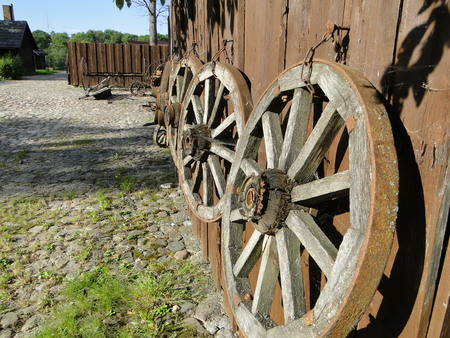 weathered wall of old barn with wooden coach wheels