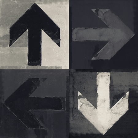 Artistic grunge design monochrome arrows, four arrow signs painted on a concrete wall   photo