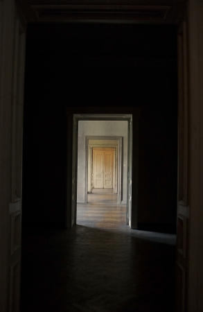 view through door: Closed door at the end of the hallway, rite of passage concept  Linear perspective view through several open doors and empty rooms