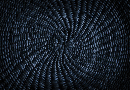Dark blue grunge abstract background from circular wicker pattern texture