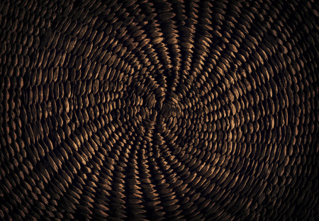 Dark brown grunge abstract background from circular wicker pattern texture photo