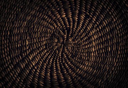 Dark brown grunge abstract background from circular wicker pattern texture Archivio Fotografico