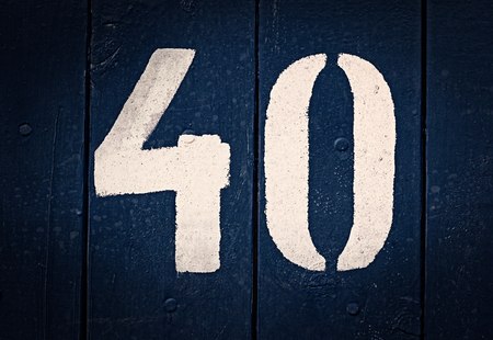 Number 40 painted on grunge navy blue aged wooden background