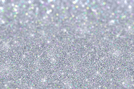 Silver glitter with colored particles defocused background