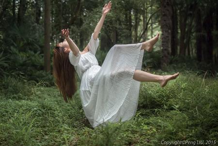 Beautiful woman falling onto the forest Foto de archivo