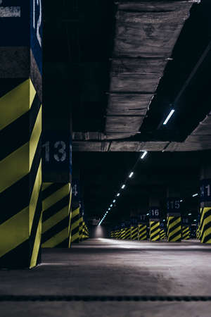 Underground parking under the supermarket, poles painted with green black stripes
