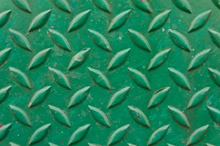 Diamond metal painted green on piece of background photo
