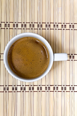 Coffee cup  on a mat made of bamboo Stock Photo