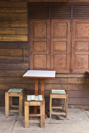Wooden tables and chairs near the old window Stock Photo