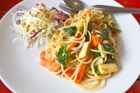 spaghetti whit shrimp and basil fried on a white dish
