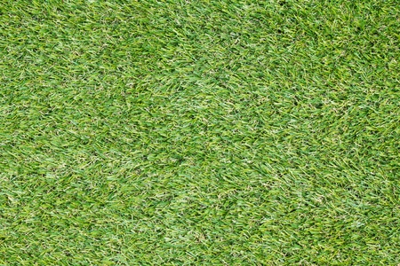 Background texture with fake grass in a public children playground, top view photo