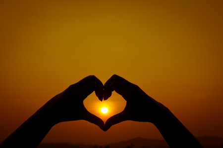 Silhouettes hand heart shaped  with sun sets and the sky orange photo