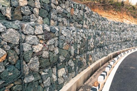 Muur rots aardverschuivingen, beschermende schanskorf muur in de bergen Stockfoto