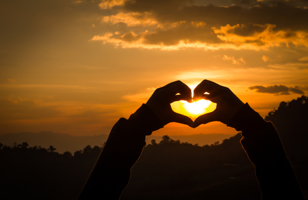 sunsets: Silhouettes hand heart shaped with sunsets and the sky orange.