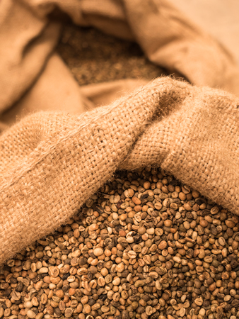 unroasted: green unroasted coffee beans in sack.