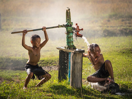 groundwater: Two young boy rocking groundwater bathe in the hot days, Countryside Thailand.