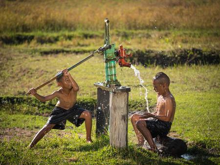 Twee jonge jongen rocken grondwater baden in de warme dagen, Platteland Thailand.