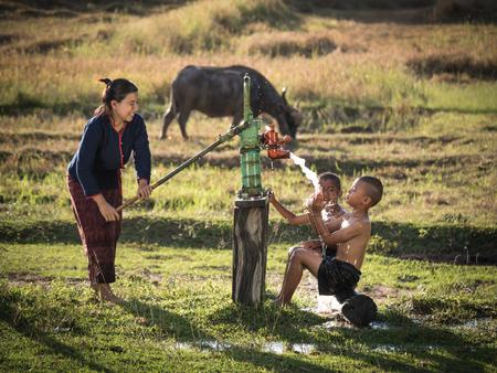 Moeder die haar zonen douche outdoor uit grondwater pomp, Aziatische vrouw en kleine jongens Platteland Thailand.