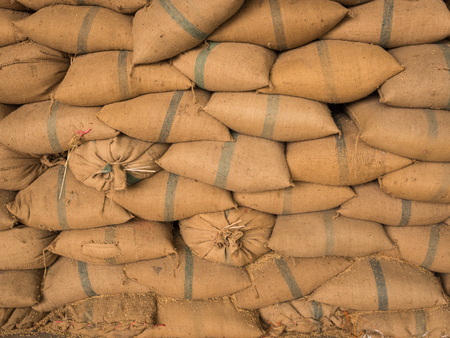 Old hemp sacks containing rice placed stacked in a row.