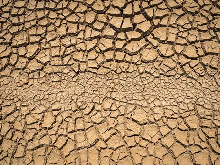Gedroogde en gebarsten grond in dorre seizoen.