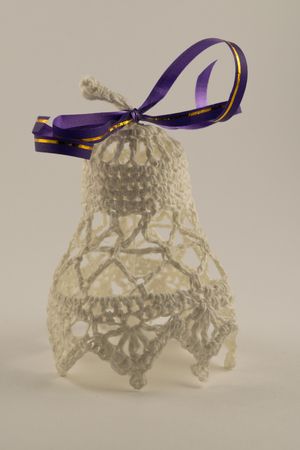 Christmas bells with purple ribbon isolated on white background. Knitted New Years bell.