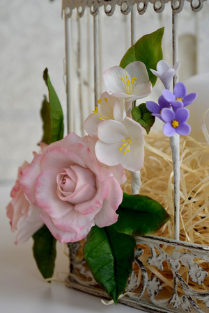 White vintage decorative bird cage with beautiful flowers.