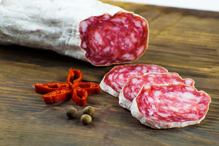 Spain sausage Salchichon. Salami on a wooden board. Stock Photo